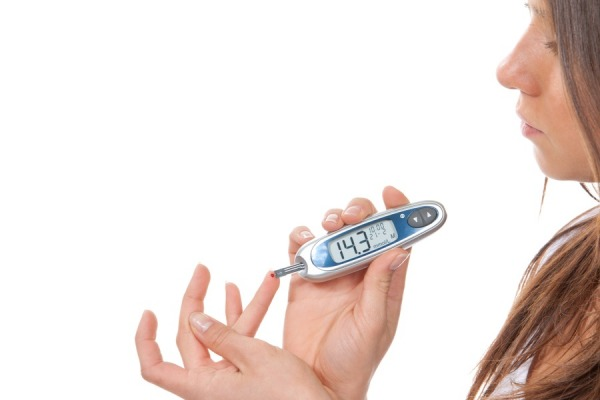 Diabetes patient woman measuring glucose level blood test with glucometer on a white background