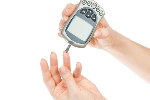 Diabetes patient measuring glucose level blood test using mini glucometer and small drop of blood from finger and test strips isolated on a white background