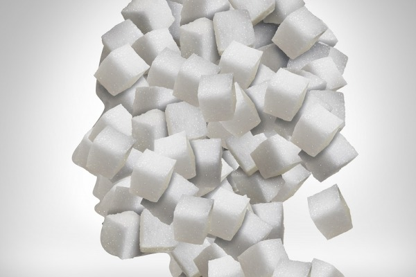 Sugar addiction concept as a human head made of white granulated refined sweet cubes as a health care symbol for being addicted to sweeteners and the medical issues pertaining to processed food.